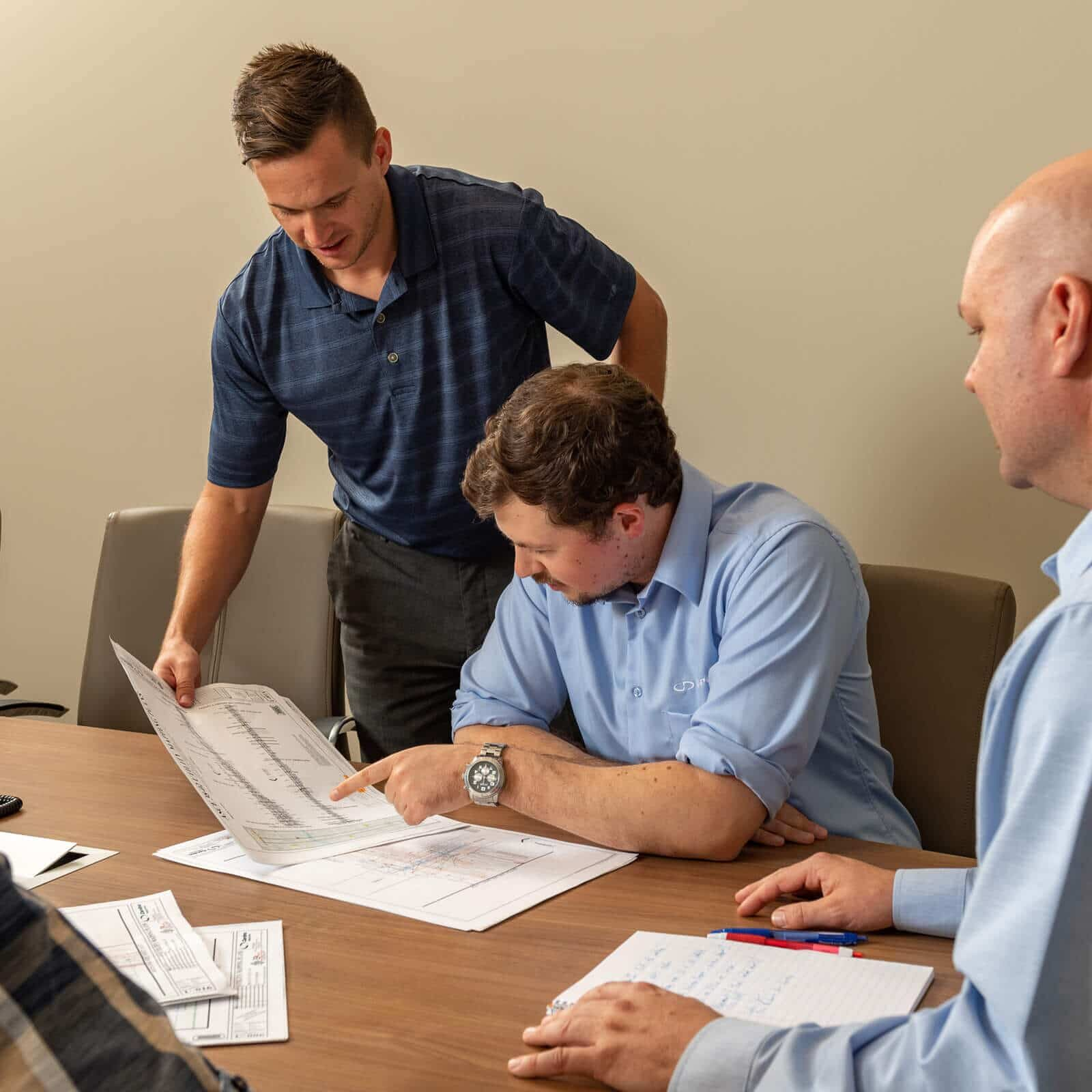 T2ue staff review plans at a conference table